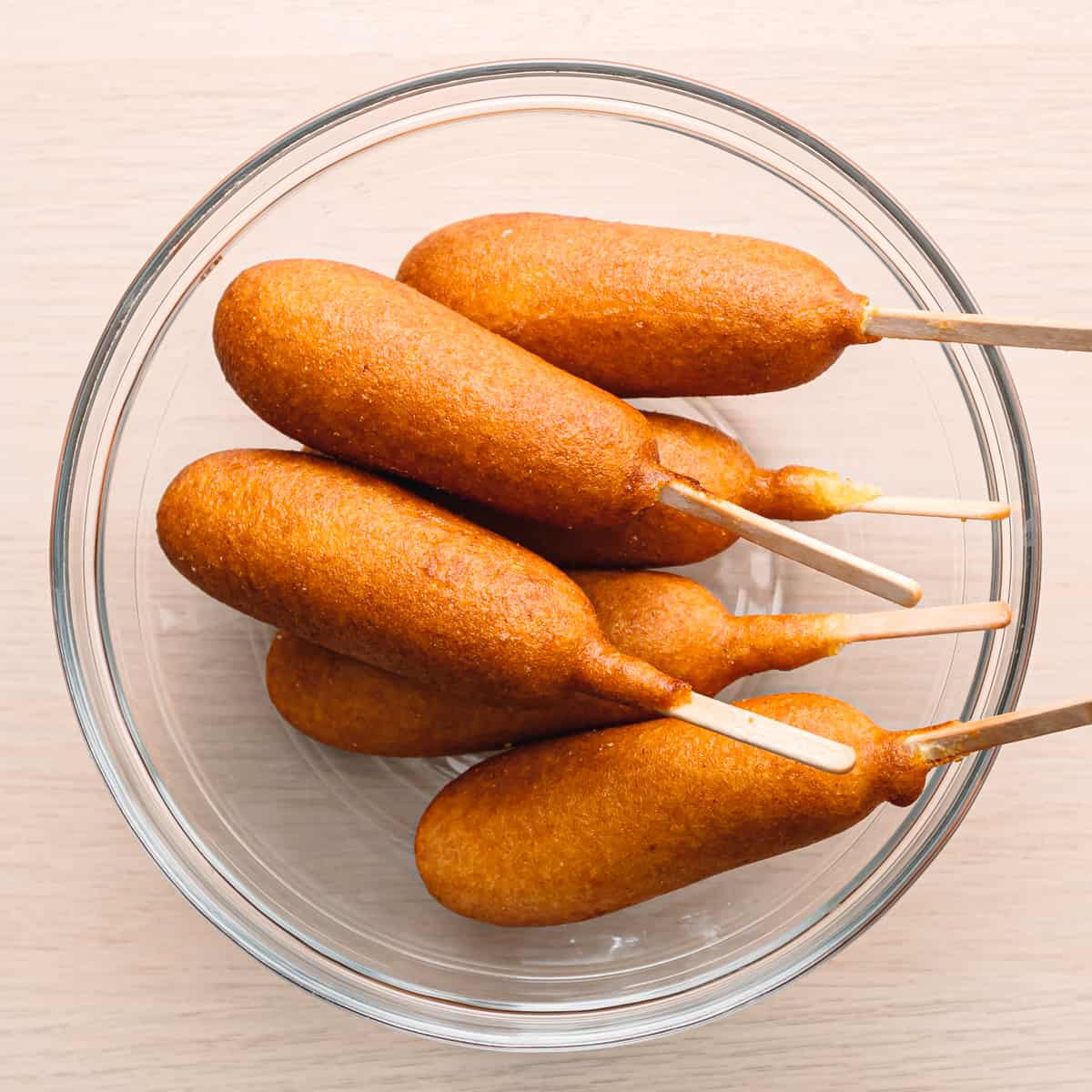 sausage on a stick is coated with a thick layer of cornmeal batter that is deep-fried.